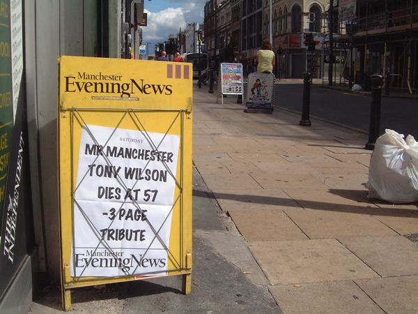 Manchester Evening News street hoarding announcing the death of Tony Wilson, set against the background of Oldham Street and Dry
